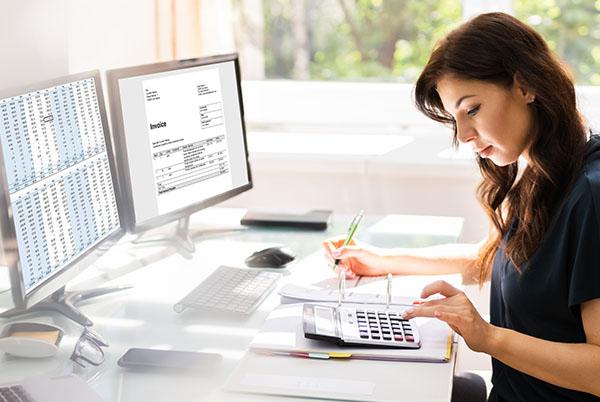 kobieta przed komputerem licząca coś nakalkulatorze